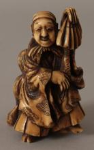 A JAPANESE MEIJI PERIOD STAINED IVORY OKIMONO OF A STREET PERFORMER, in the company of his son, the man holding aloft an upturned fan, 2.75in high.