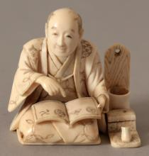 A SIGNED JAPANESE MEIJI PERIOD IVORY OKIMONO OF A STREET SCRIBE, kneeling with an open book and with his implements beside him, the base with an engraved signature on a red lacquer reserve, 1.9in wide & also 1.9in high.