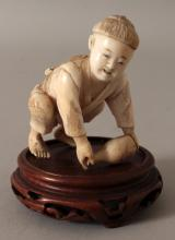A JAPANESE IVORY OKIMONO OF A BOY, together with a fixed wood stand, the boy bending forward to lift a sake flask from the ground, 3.2in high overall, the ivory itself 2.3in high.