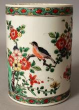 A GOOD CHINESE KANGXI PERIOD FAMILLE VERTE PORCELAIN BRUSHPOT, circa 1700, the sides well painted with a continuous scene of birds perched on blossoming boughs above rockwork, 4in diameter at base & 5.6in high.