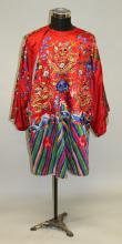 AN EARLY 20TH CENTURY CHINESE RED GROUND EMBROIDERED SILK DRAGON ROBE, decorated in satin stitch and gilt thread with dragons, ribboned emblems, floral sprays and clouds above stylised waves to the hem, approx. 41.5in high.