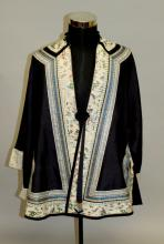 AN EARLY 20TH CENTURY CHINESE BLACK GROUND SILK JACKET, with patterned dragon roundels, the hems with embroidered cream-ground silk borders decorated with ladies in garden and terrace settings, approx. 36.5in high.