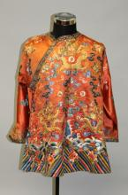 A GOOD QUALITY EARLY 20TH CENTURY CHINESE ORANGE GROUND EMBROIDERED SILK DRAGON ROBE, decorated in satin stitch and gilt thread with dragons, ribboned emblems, bats and cloud scrolls above stylised waves and rocks, approx. 31in high.
