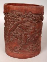 A CHINESE BAMBOO BRUSHPOT, decorated in relief with sages in a continuous landscape setting, 5.1in wide at widest point on base & 6.3in high.