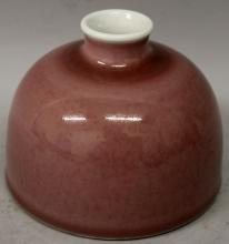 A CHINESE PEACH BLOOM PORCELAIN WATER POT, applied with a pale mottled glaze, the base with a six-character Kangxi mark, 5.1in diameter at base & 3.9in high.