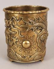AN EARLY 20TH CENTURY CHINESE POLISHED BRONZE BRUSHPOT, cast in relief with a dragon pursuing a flaming pearl above waves, the base cast with a seal mark, 5.6in diameter at rim & 6.1in high.