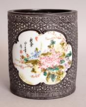 AN UNUSUAL CHINESE FAMILLE ROSE & BRONZED PORCELAIN BRUSHPOT, decorated with two scroll bordered floral panels reserved on an imitation bronze trellis ground, the base with a moulded Qianlong seal mark, 3.75in diameter at base & 4.5in high.