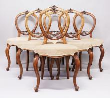 A SET OF SIX VICTORIAN WALNUT BALLOON BACK DINING CHAIRS, with carved decoration, overstuffed seats, on cabriole legs.