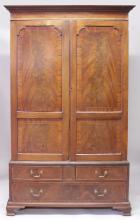 A GEORGIAN MAHOGANY HANGING WARDROBE, with a pair of double panel doors enclosing hanging space, with two small and one long drawer below with brass handles, supported on bracket feet. <br>6ft 10ins high, 3ft 10ins wide.