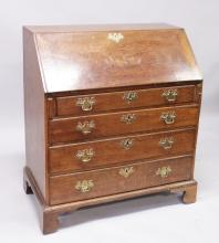 A GOOD GEORGE III OAK BUREAU, with fall front and fitted interior, over four long graduated drawers with brass handles, supported on bracket feet. <br>2ft 11ins wide.
