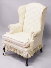A WING ARMCHAIR on cabriole legs with pad feet.