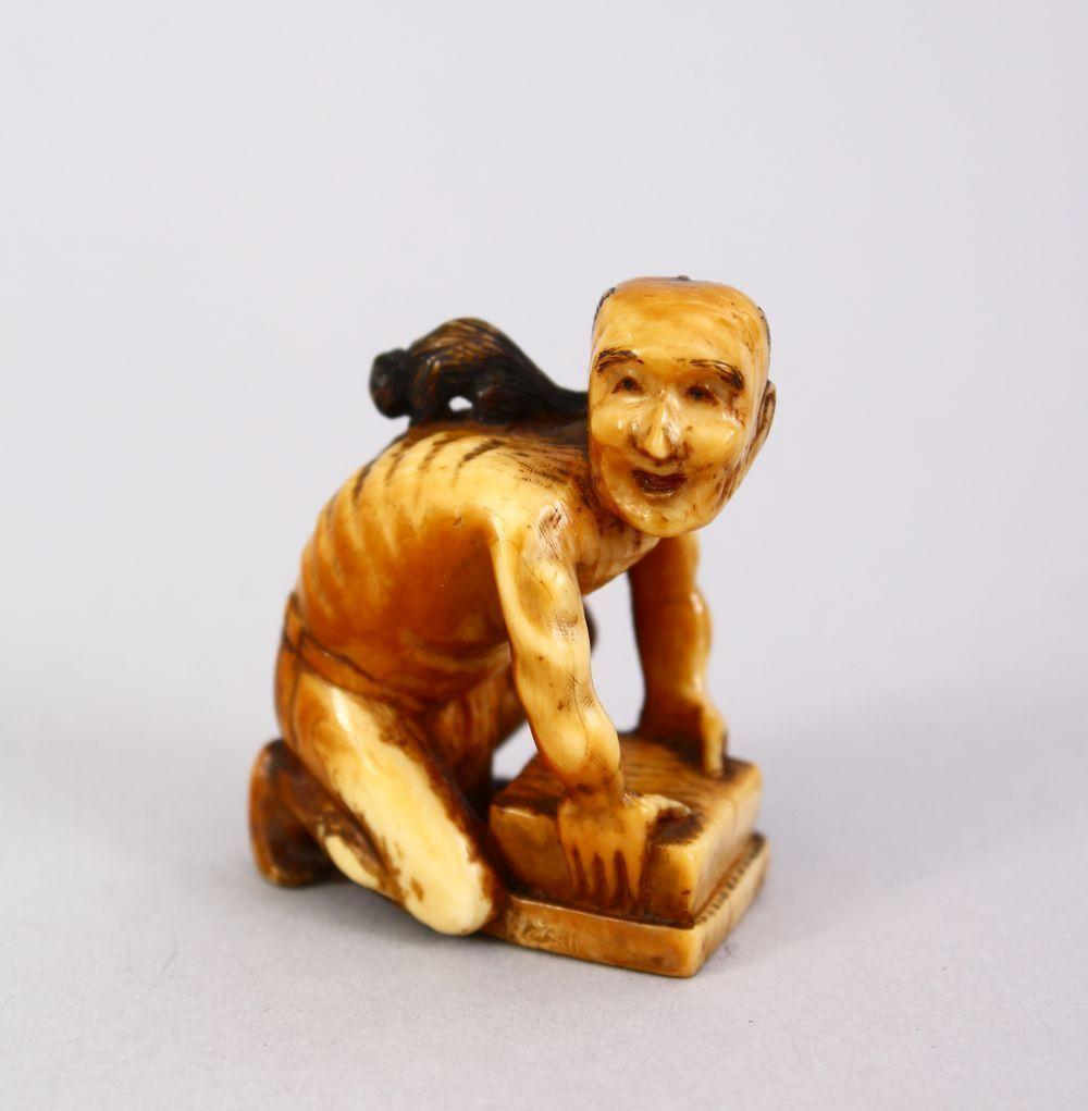 A JAPANESE MEIJI PERIOD CARVED IVORY SMALL OKIMONO OF A RAT CATCHER, the man leaning over his trap with the ra