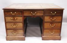 A GEORGE III MAHOGANY PEDESTAL PARTNERS DESK with gilt tooled leather inset top, pull out slides to each end, each side having a central frieze drawer and four graduated drawers to each pedestal, all with brass swan neck handles, supported on plinth bases. <br>4ft 7.5ins wide x 3ft 7.5ins deep x 2ft 8ins high.
