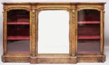 A VICTORIAN BURR WALNUT AND ORMOLU BREAKFRONT CREDENZA, with a central mirrored door, flanked by glazed doors on a plinth base. <br>6ft 6ins long, 3ft 6ins high x 1ft 4ins deep.