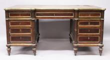 A FRENCH EMPIRE MAHOGANY AND BRASS INLAID PEDESTAL DESK, with shaped rectangular top, leather writing surface, three frieze drawers, the pedestals with three drawers and cupboard doors to the reverse, flanked by reeded columns on turned feet. <br>5ft 0ins long x 2ft 7ins wide x 2ft 6ins high.