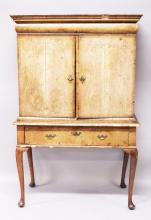A QUEEN ANNE WALNUT CABINET ON STAND, with a moulded cornice, cushion drawer, pair of doors enclosing an arrangement of drawers and a small cupboard, on a stand with one long drawer, and later cabriole legs. <br>5ft 6ins high x 3ft 6ins wide x 1ft 8ins deep.