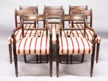 A SET OF EIGHT GEORGE IV MAHOGANY DINING CHAIRS, two with arms, rope backs, padded seats, on turned and tapering legs.