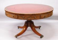 A GEORGIAN MAHOGANY CIRCULAR DRUM TABLE, 4ft 3ins diameter, the top with leather writing panel and alternate drawers with circular brass handles, on a centre support with quadruple curving legs and brass castors.