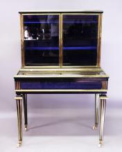 A SUPERB LOUIS XVI STYLE VITRINE, CIRCA. 1880, the top with a pair of glass doors enclosing two shelves and a blue velvet interior, on a base with lift-up glass doors opening to reveal a blue velvet interior, and supported on tapering legs with white porcelain castors. <br>3ft 3ins wide, 1ft 8ins deep, 4ft 11ins high.