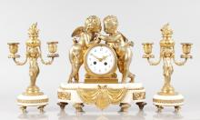 A GOOD LOUIS XVI DESIGN WHITE MARBLE AND ORMOLU THREE PIECE CLOCK GARNITURE, Retailed by Maple & Co., the clock with eight-day movement, with two cupids, 13ins high, complete with a pair of two branch candlesticks with cupid supports, 12ins high.