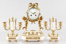 A SMALL LOUIS XVI DESIGN WHITE MARBLE AND GILT METAL THREE PIECE CLOCK GARNITURE, the clock with drum movement  held by two cupids, 13ins high, complete with a pair of two light sticks, 9ins high.