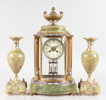 A VERY GOOD 19TH CENTURY FRENCH CHAMPLEVE ENAMEL THREE PIECE CLOCK GARNITURE, Retailed by MACKAY BROS., DUNDEE, the superb clock with urn surmount, column sides and serpentine front, eight-day movement, 18.5ins high, complete with a matching pair of urns, 12ins high.