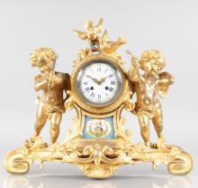 A GOOD LOUIS XVI ORMOLU AND SEVRES PORCELAIN MANTLE CLOCK, with eight-day movement, circular dial with blue and white Roman numerals, the case with two cupids with bows, two birds and acanthus scrolls. <br>16ins high, 19ins wide.
