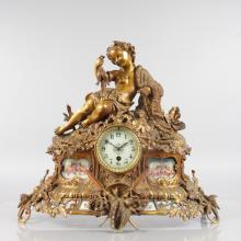 A GOOD LOUIS XVI ORMOLU AND SEVRES PORCELAIN MANTLE CLOCK, with eight-day movement, cream dial, the case with a young girl carrying fish with painted Sevres panels, shells, acanthus, cross oars etc. <br>18ins high, 19ins long.