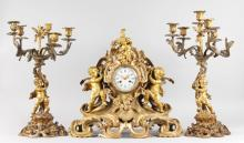 A GOOD LOUIS XVI ORMOLU THREE PIECE CLOCK GARNITURE, the clock by TILFACQ DURDAN A. LILLE with circular dial, blue and white Roman numerals, eight-day movement, No. 2737, striking on a single bell, the case with three cupid and acanthus scrolls, 20ins high, 20ins wide, complete with a pair of matching five light candelabra, 23ins high.