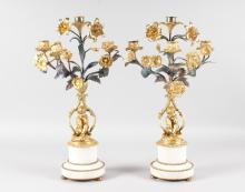 A GOOD PAIR OF LOUIS XVI PATTERN ORMOLU AND WHITE MARBLE FOUR LIGHT CANDELABRA, formed as cupids sitting beneath scrolling branches and supported on circular white marble pedestals. <br>18ins high.
