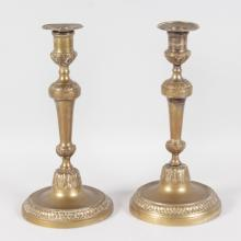 A PAIR OF LOUIS XVI GILT METAL ETCHED CANDLESTICKS with beaded edge rims. <br>11ins high.