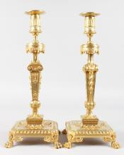 A PAIR OF LOUIS XVI ORMOLU CANDLESTICKS, on pierced square bases with claw feet. <br>15ins high.