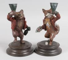 A PAIR OF PAINTED COLD CAST AMUSING FOX CANDLESTICKS on circular bases. <br>7ins high.
