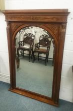 A LARGE EMPIRE MAHOGANY UPRIGHT MIRROR with sphinx mount and oval mirrored panel. <br>5ft high.