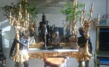 A LARGE PAIR OF PAINTED WOOD BLACKAMOOR STANDING CANDELABRA holding large gilt cornucopia, each with six scrolling branches. <br>6ft 4ins high.