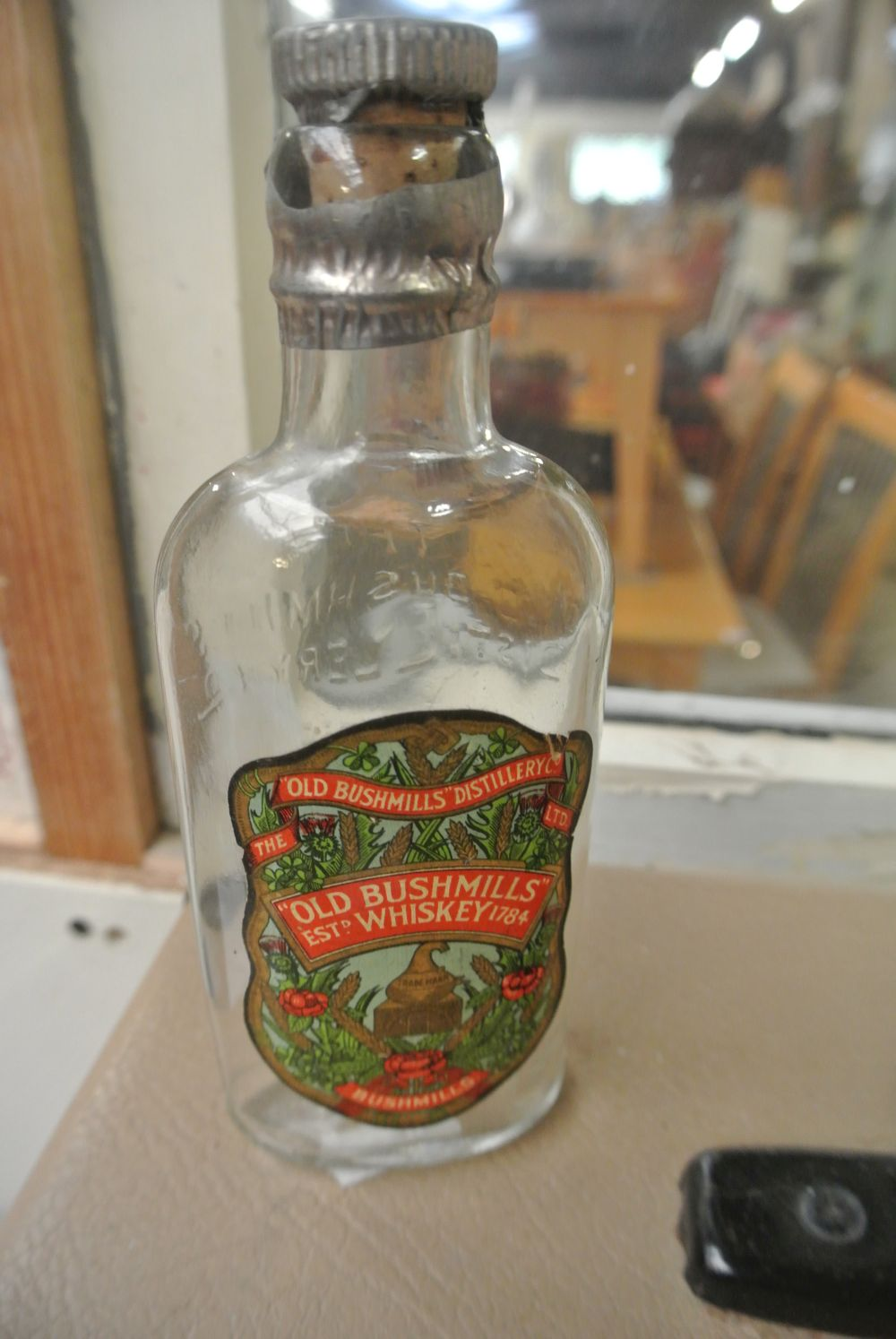 An antique glass bottle, with original 'Old Bushmills Whiskey