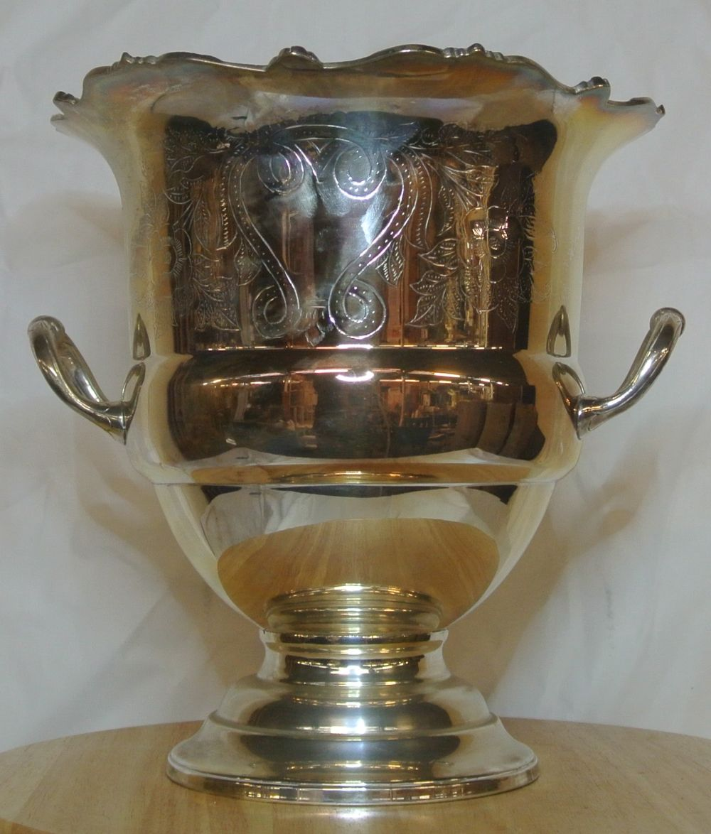 An antique style silver plated ice bucket with decorative design.