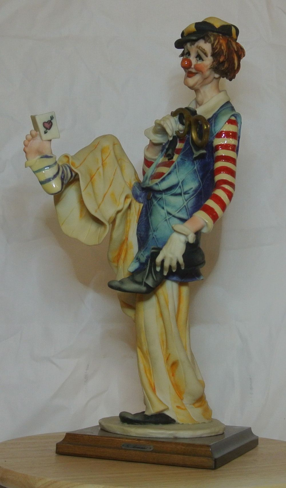 A Capodimonte figure of a clown reading a book held between his toes