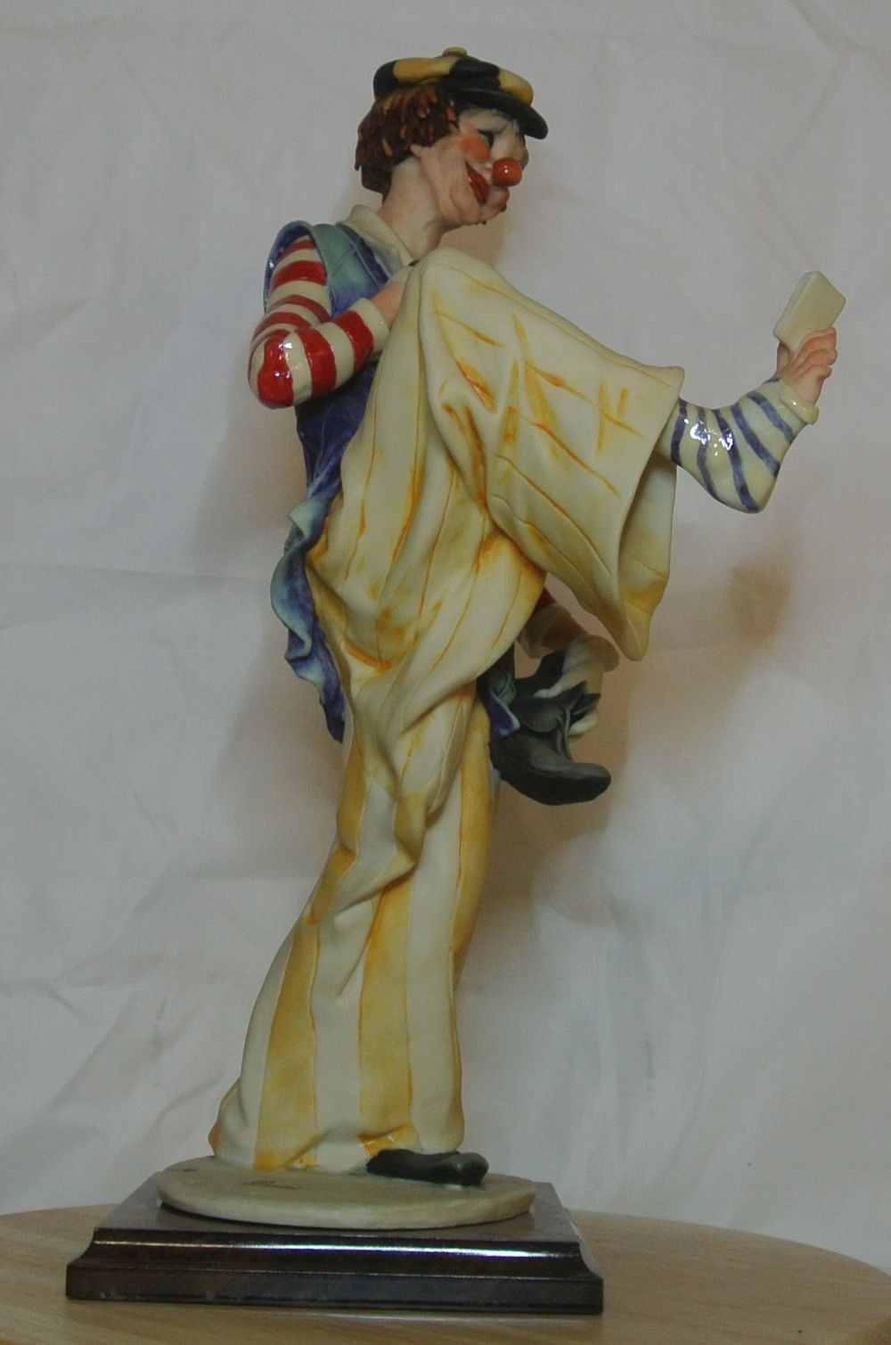 Lot 78: A Capodimonte figure of a clown reading a book held between his toes