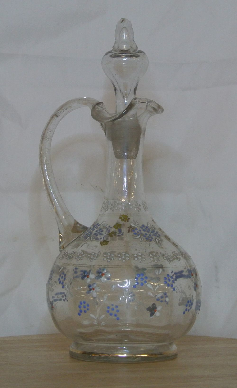 An antique hand painted glass claret jug