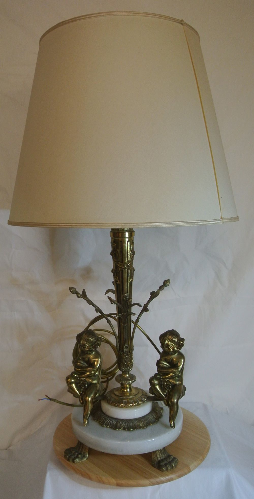 A large ornate gilt table lamp with cherub base & cream shade.