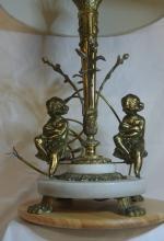 Lot 125: A large ornate gilt table lamp with cherub base & cream shade.