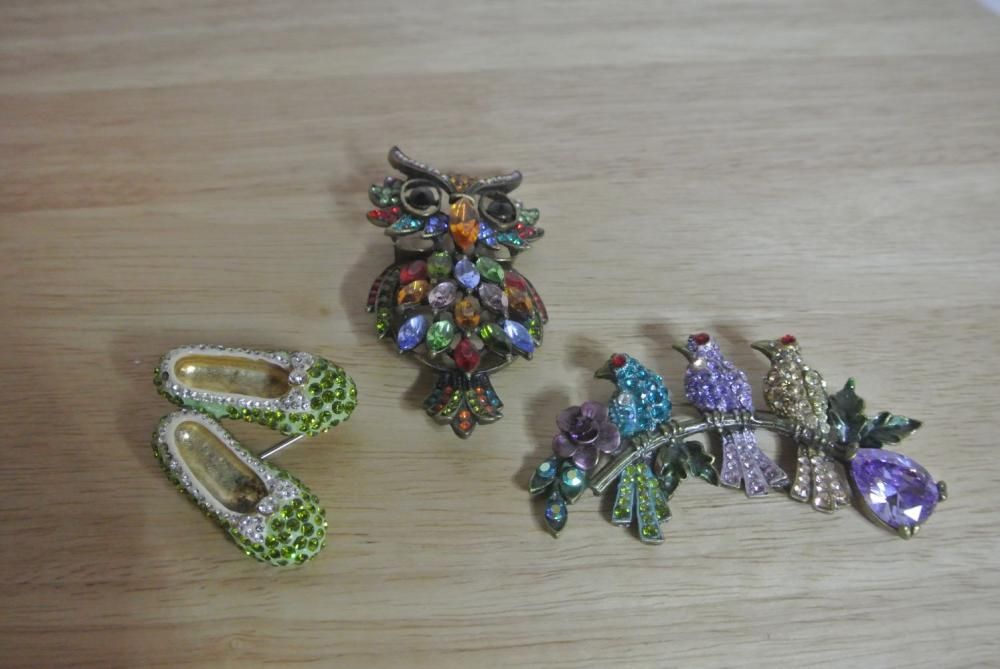 A collection of 3 decorative brooches.