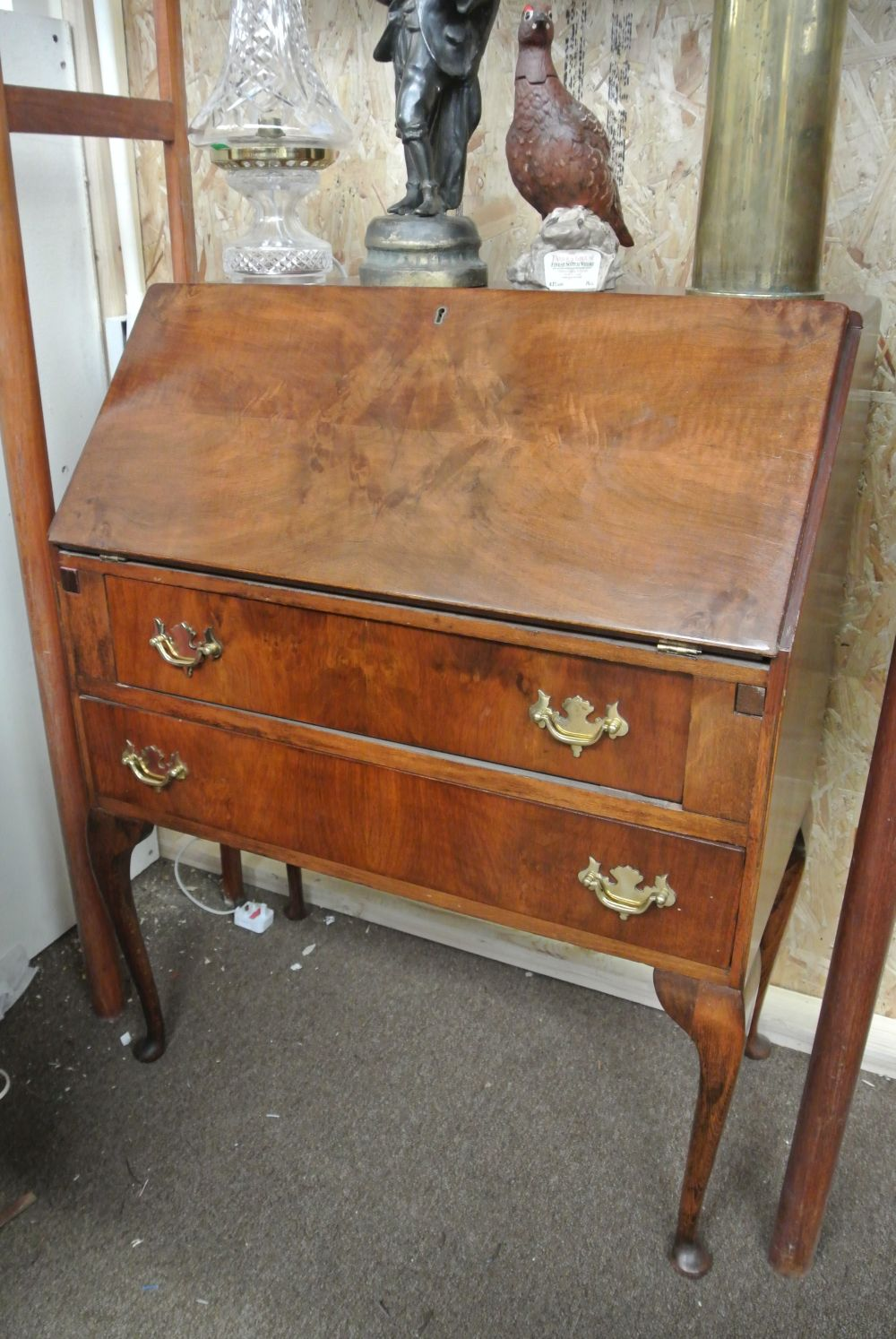 An antique writing bureau on cabriole legs with brass hardware.