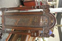 Lot 131: An antique hall chair with carved frame