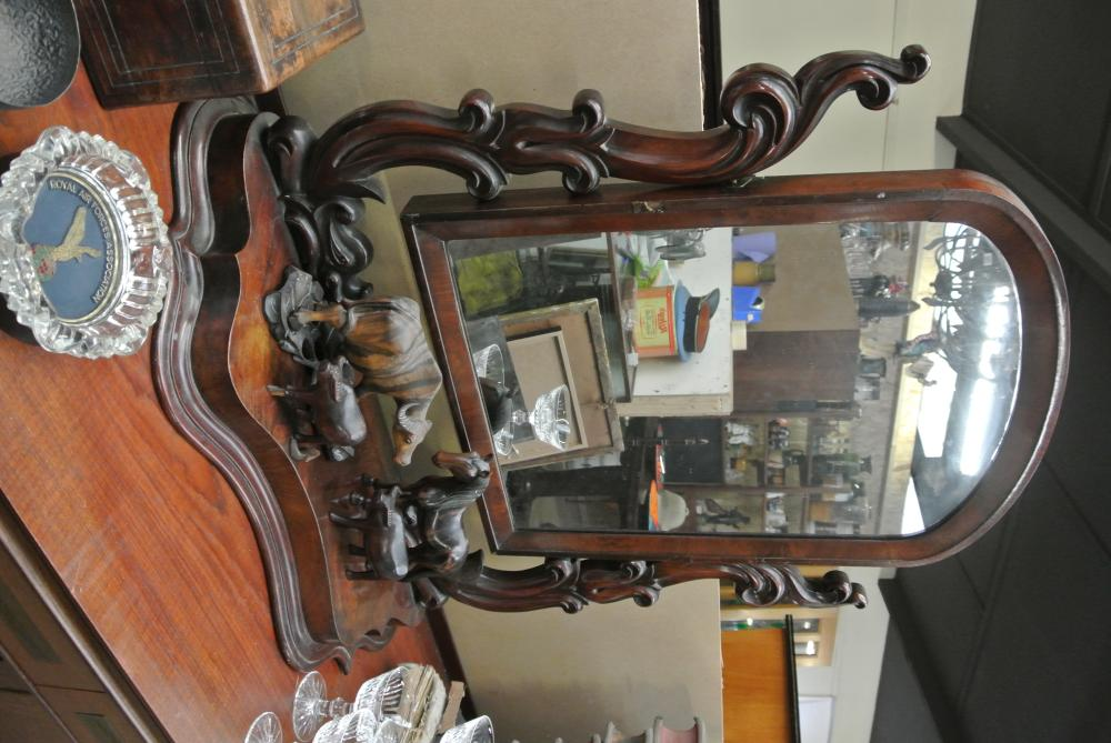 A large antique dressing table mirror with carved supports.