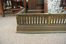 Lot 150: An antique brass fire fender with pierced design.