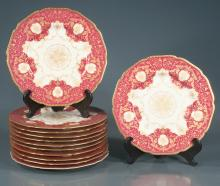 Set of 12 Bavarian china dinner plates in ivory and puce having raised gilt scrolling decoration, 10.5