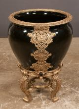 Black oriental porcelain fish bowl having elaborate brass mounts raised on brass stand, 20
