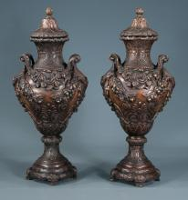 Pair of bronze double handled capped pedestal urns having foliate and floral garland decoration, 21